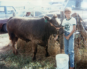 Childhood photo for Dr. Laura Beane Freeman standing next to a cow.